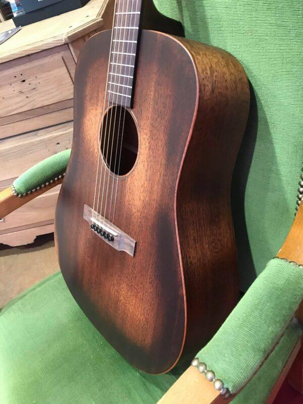 profil guitare acoustique posée sur fauteuil vert