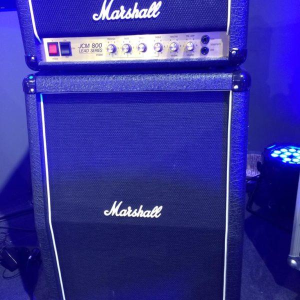 ampli guitare noire et or avec une tête et un baffle