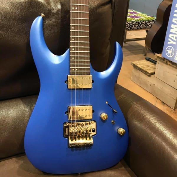 guitare électrique bleue posée sur canapé marron