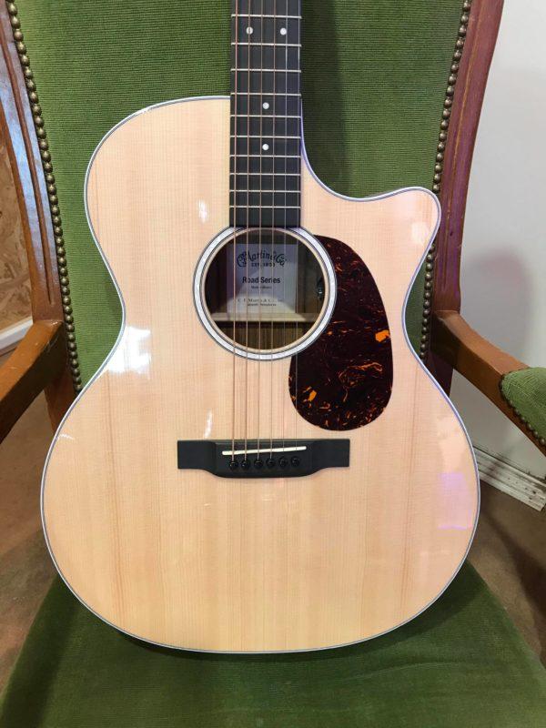 guitare folk électro posée sur fauteuil vert