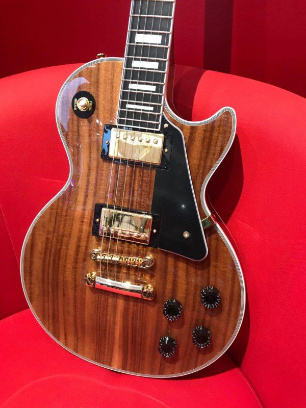 guitare électrique marron dans fauteuil rouge
