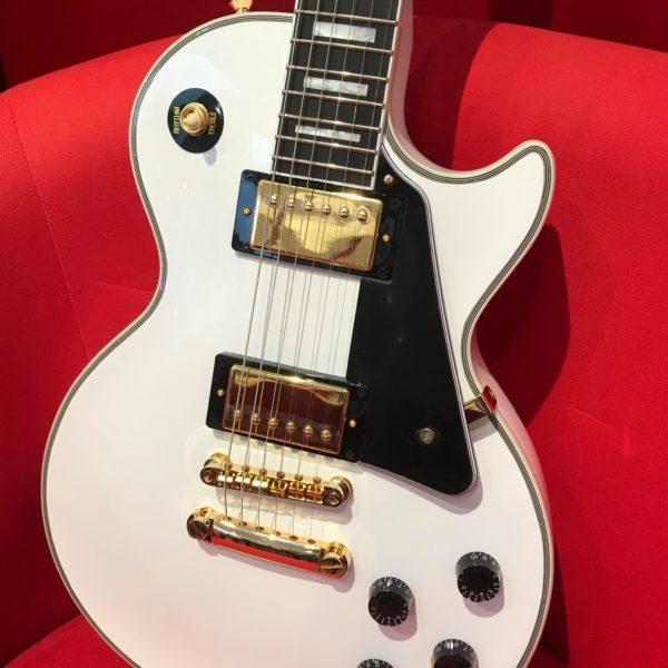 guitare blanche dans fauteuil rouge