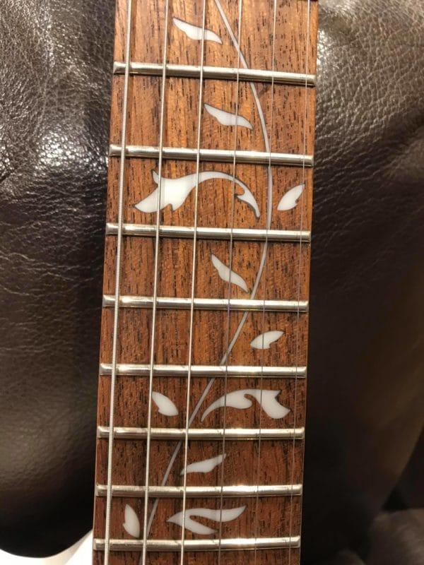 manche de guitare avec fleurs blanches