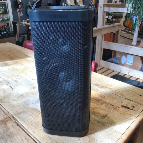 enceinte portative noire posée sur table bois