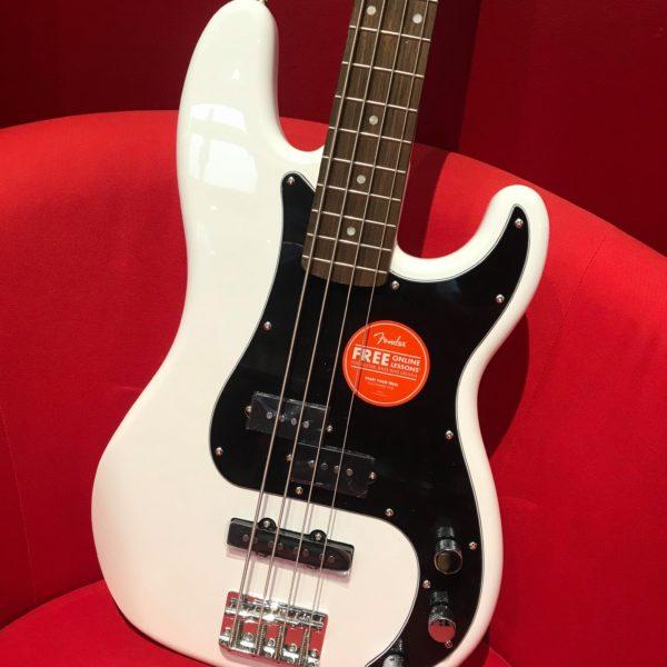 guitare basse blanche posée sur fauteuil rouge
