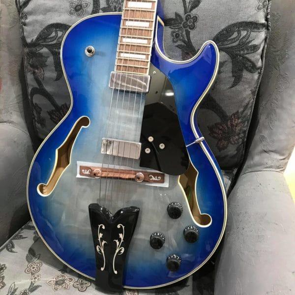 guitare bleue électrique posée sur fauteuil gris