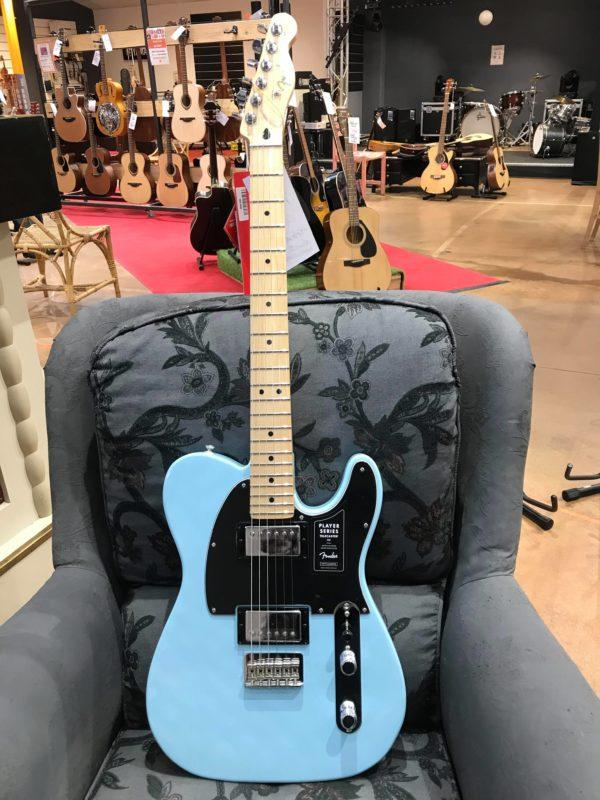 guitare électrique bleu posée sur fauteuil