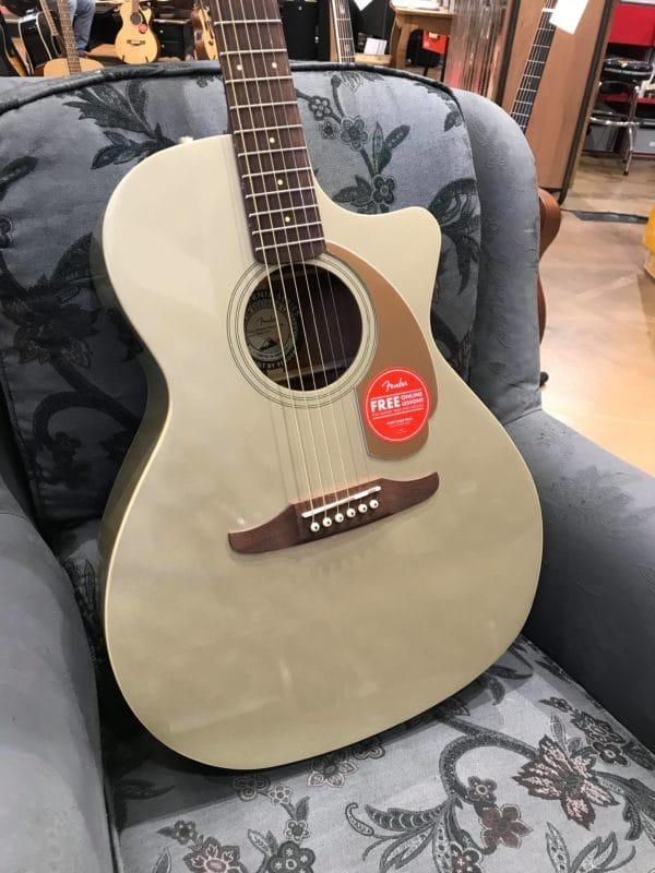 guitare électro acoustique grise sur fauteuil gris