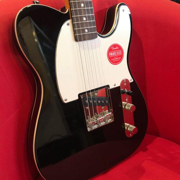 guitare électrique noire et blanche sur un fauteuil rouge