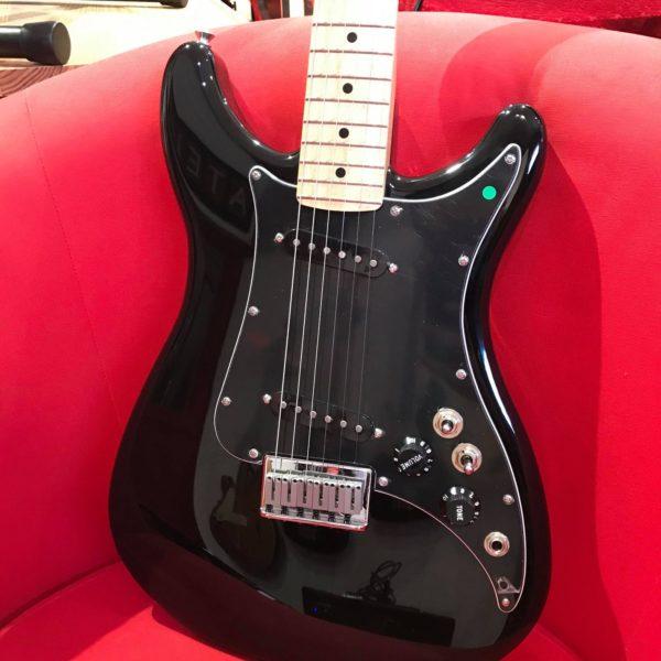 guitare électrique noire posée sur fauteuil rouge