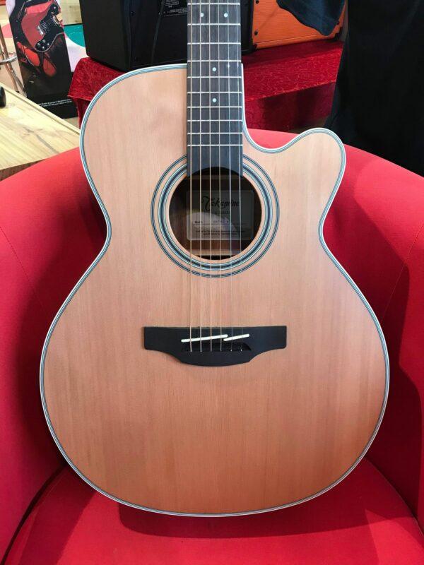 corps de guitare acoustique sur fauteuil rouge