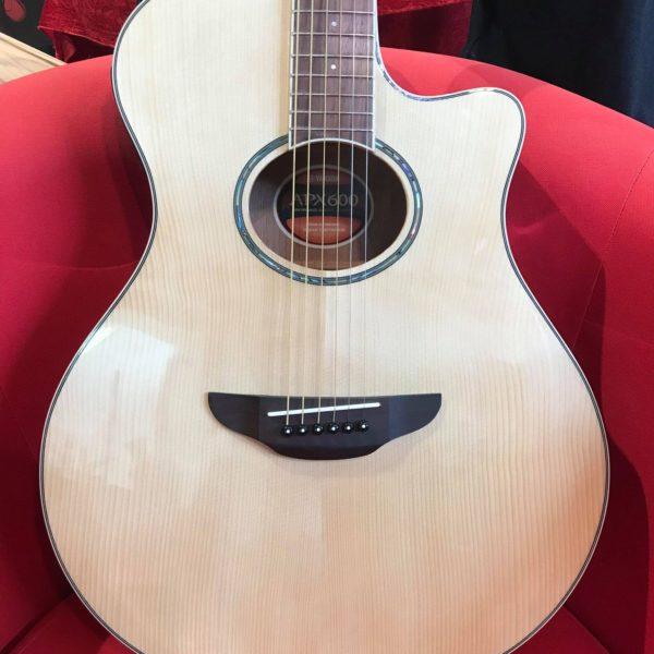 guitare électro acoustique sur fauteuil rouge
