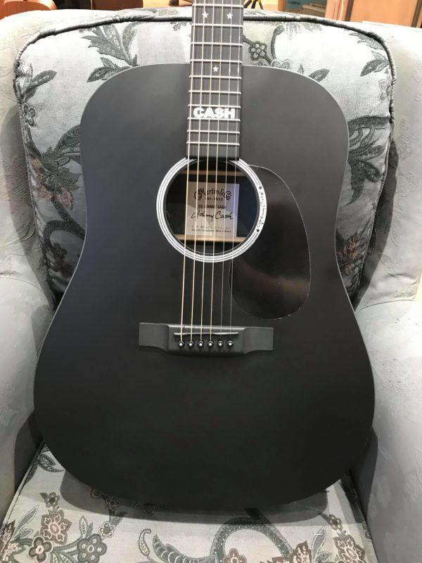 guitare acoustique noire posée sur fauteuil