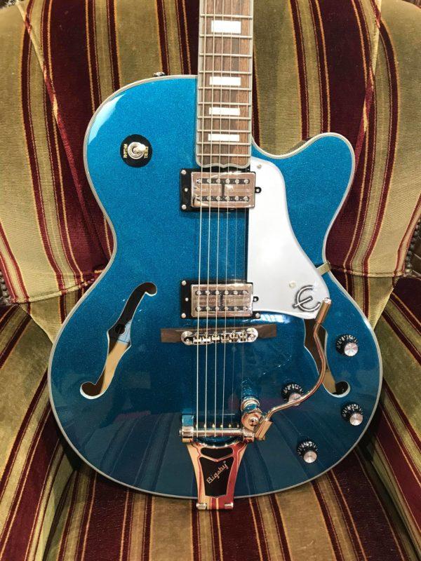 guitare électrique bleue paillette posée sur canapé